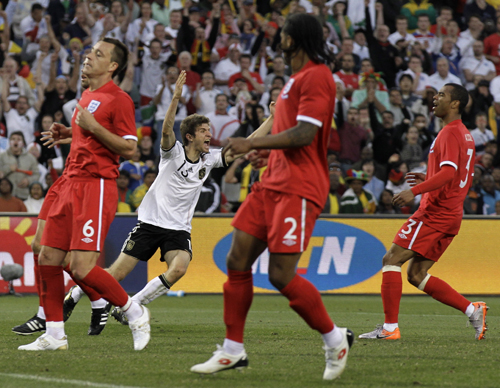 Ashley Cole, til høyre, iført den lite vellykkede røde England-drakten over en rød undertrøye.